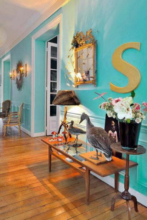 Dans le couloir, jeux de constrastes entre une table basse en teck surmontée d'un miroir style Louis XVI et la lampe en bois de cerf avec abat-jour en