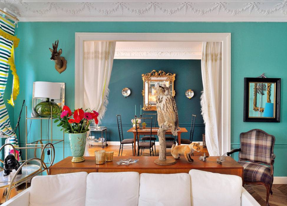 Le camaïeu de verts et les rideaux à franges de plumes  de Stella Cadente, séparent visuellement le salon de la salle à manger. Table en teck au design scandinave des années 50, chaises chinées à Bruxelles.  « Une maison doit avoir un vrai look. Je m'amuse à mélanger époques, matières, styles, coloris avec harmonie. »