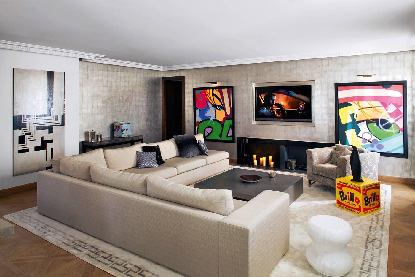 Au salon TV, canapé sur mesure de Stéphanie Coutas et tissus Armani, table basse « Danica » (Armani Casa), tapis Pierre Frey Braquenié. Au mur, œuvres originales de  « Crash » John Matos.