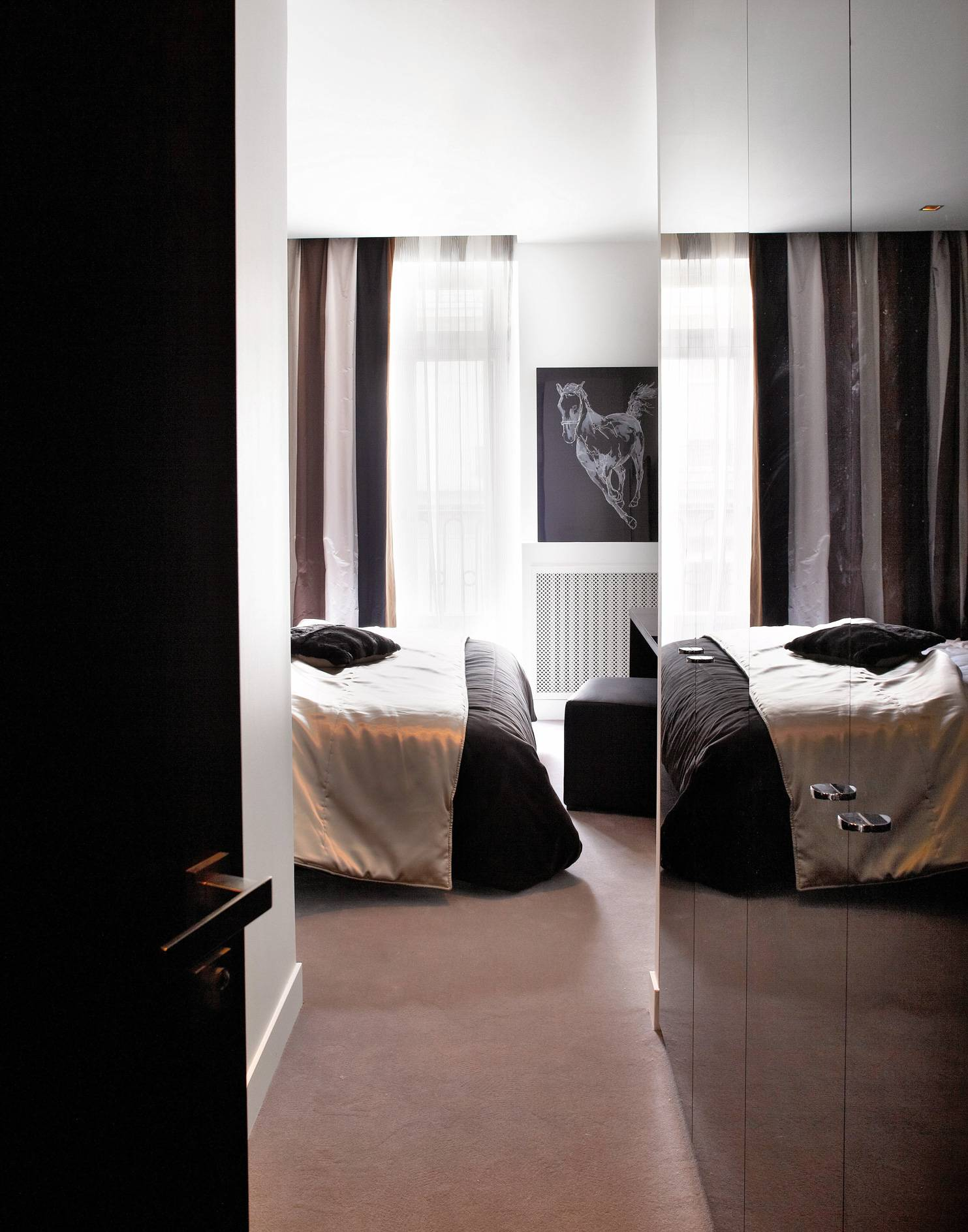 Dans une suite parentale, ambiance moirée reflétée par les portes du placard sur-mesure Quadro, couvre-lit Elitis ; pouf carré Marina Sièges, rideaux et coussins  de (Designers Guild), tapis Bomat.
