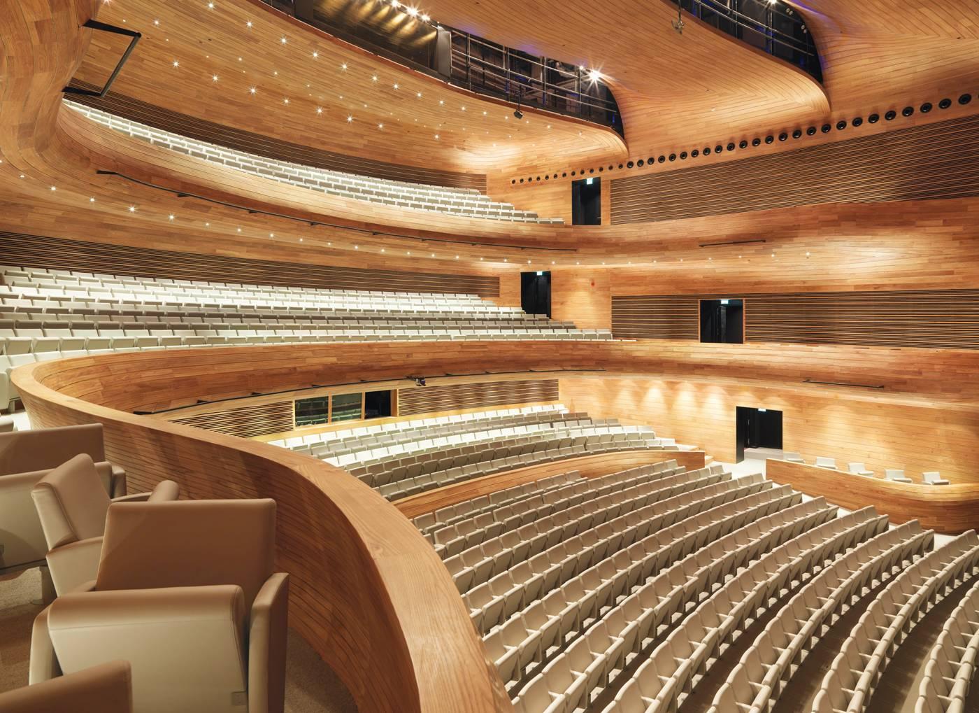 La salle aux  formes organiques  est entièrement  revêtue d'orme, bois sélectionné pour ses qualités acoustiques.