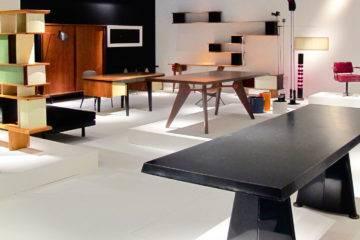 Au premier plan de ce stand mis en scène sur une des nombreuses foires internationales auxquelles participe François Laffanour, la table « Trapèze » en tôle d'acier pliée laquée noire a été conçue pour aménager la Cité Universitaire d'Antony.